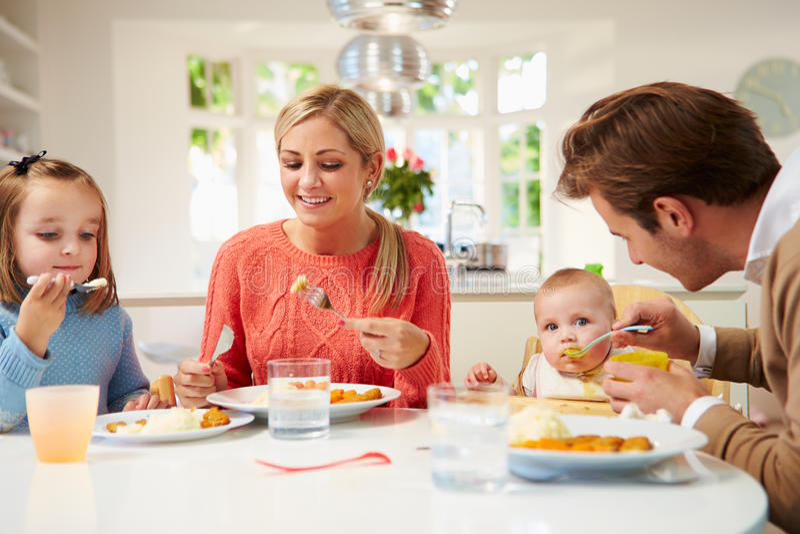 Familie met Jonge Baby die Maaltijd thuis eten royalty-vrije stock foto
