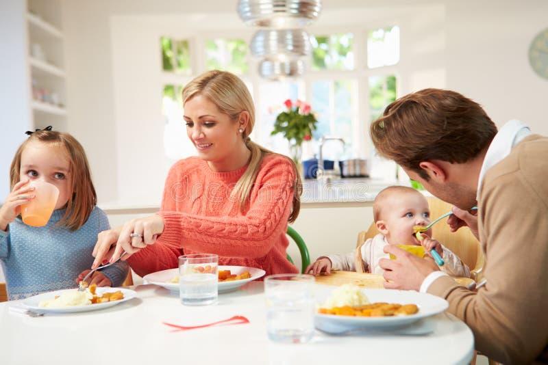 Familie met Jonge Baby die Maaltijd thuis eten stock fotografie