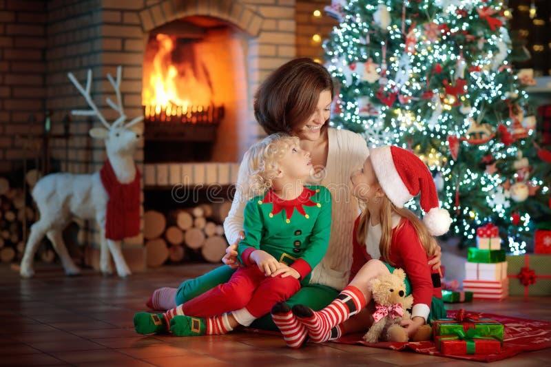 Familie met jonge geitjes bij Kerstboom en open haard stock afbeeldingen