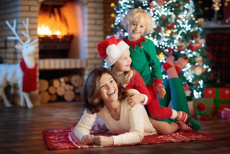 Familie met jonge geitjes bij Kerstboom en open haard royalty-vrije stock fotografie
