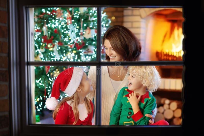 Familie met jonge geitjes bij Kerstboom en open haard royalty-vrije stock foto