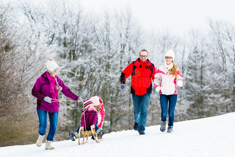 Familie met jonge geitjes die de wintergang in sneeuw hebben stock foto's