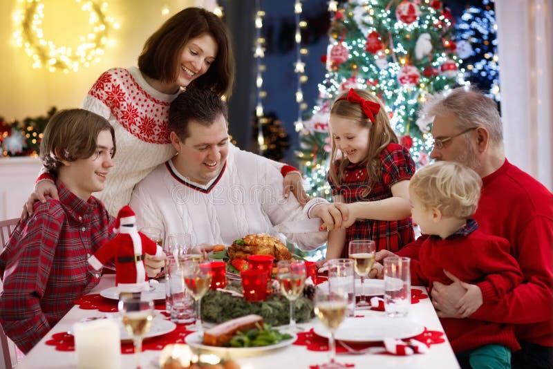 Familie met jonge geitjes die Kerstmisdiner hebben bij boom royalty-vrije stock afbeelding