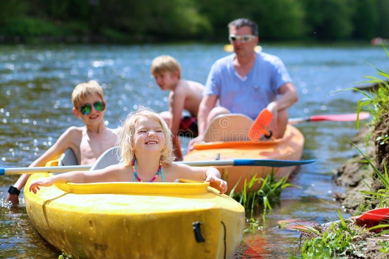 Familie met kinderen die op de rivier kayaking stock afbeelding