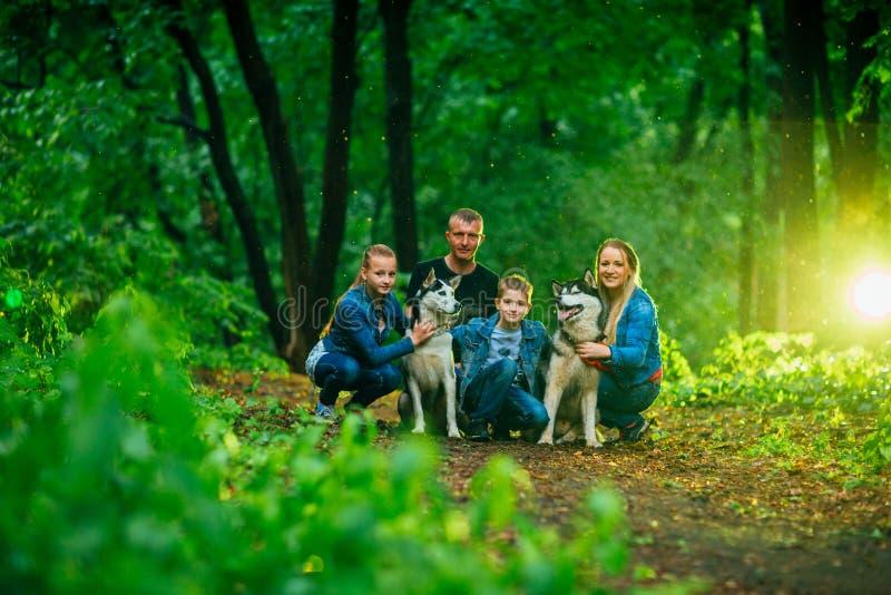 Familie met kinderen, en schor honden in het bos royalty-vrije stock afbeeldingen