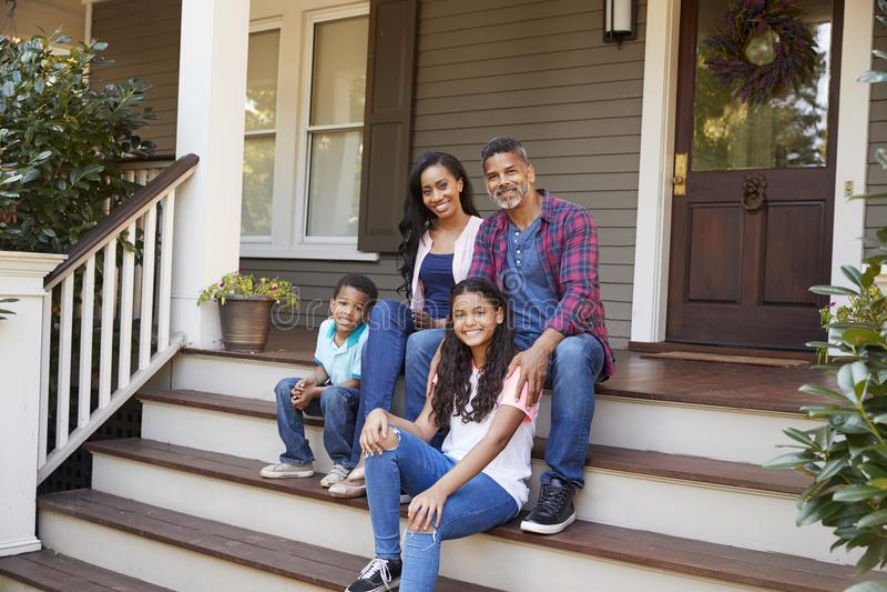 Familie met Kinderen Sit On Steps Leading Up aan Portiek van Huis royalty-vrije stock foto