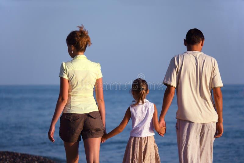 Familie met meisjesgangen langs overzees strand. Achter mening. stock foto