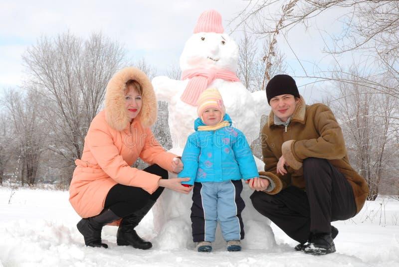 Familie met sneeuwman stock foto's