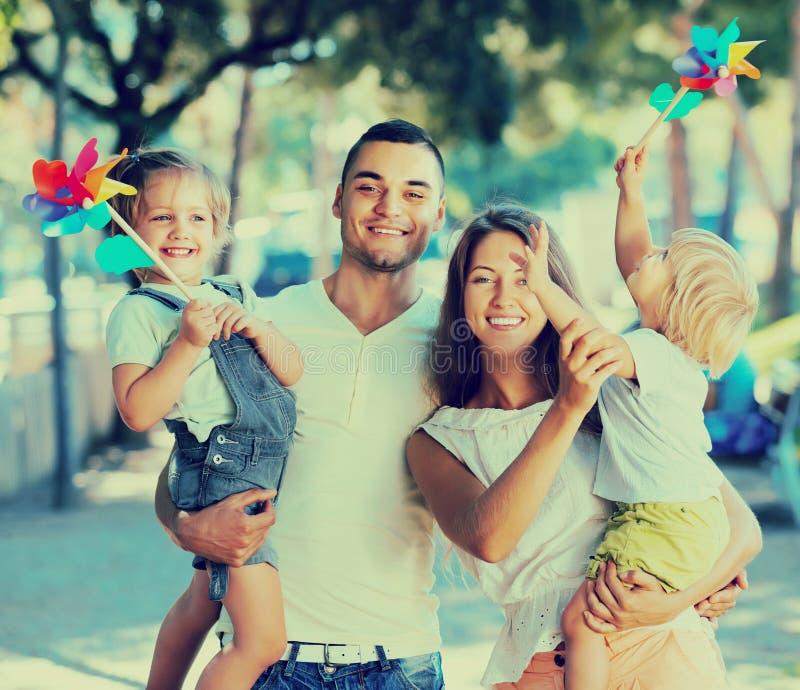 Familie met stuk speelgoed windmolens bij park stock fotografie