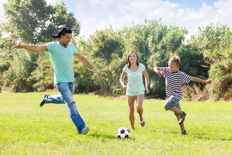 Familie met tiener het spelen in voetbal stock afbeeldingen