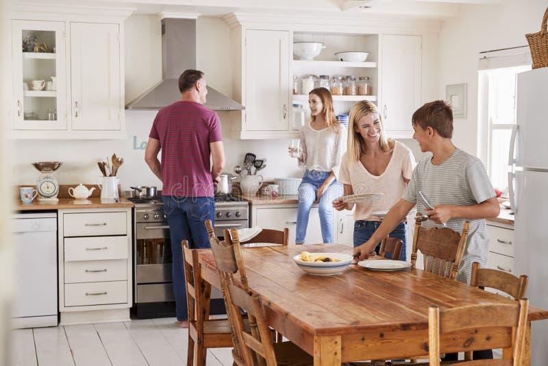 Familie met Tienerkinderen die Lijst voor Maaltijd in Keuken leggen stock foto