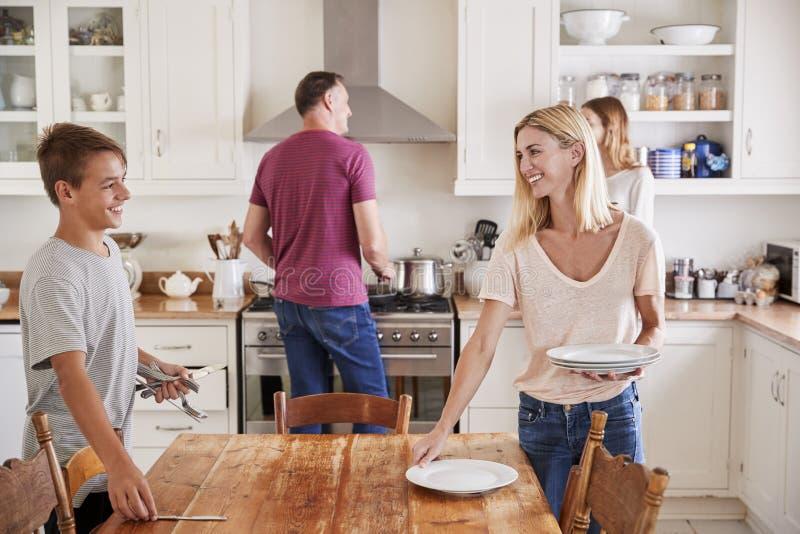 Familie met Tienerkinderen die Lijst voor Maaltijd in Keuken leggen stock fotografie
