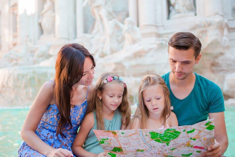 Familie met toeristische kaart dichtbij Fontana Di Trevi, Rome, Italië De gelukkige vader en de jonge geitjes genieten binnen van stock afbeeldingen