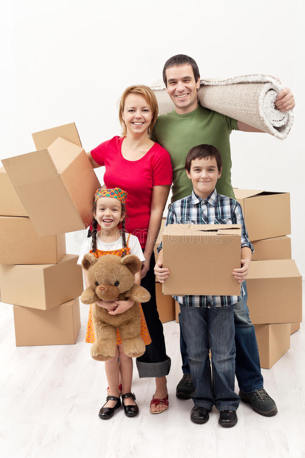 Familie met twee jonge geitjes die zich aan een nieuw huis bewegen stock foto