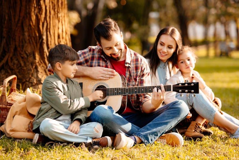 Familie met twee kinderen die op een picknickdeken zitten in een park terwijl papa het spelen royalty-vrije stock foto