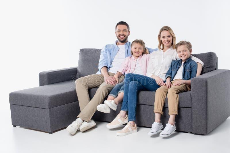 Familie met twee kinderen die samen op laag zitten en bij camera glimlachen stock fotografie
