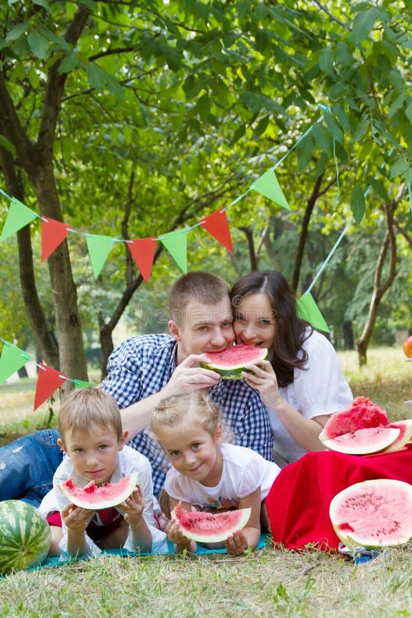 Familie met twee kinderen die watermeloenen op picknick eten openlucht stock afbeelding