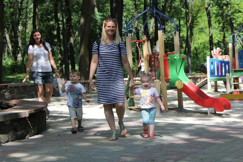 Familie met twee kinderen Moeder en siblings jonge geitjes die pret in openlucht in tuin hebben, die in de zomerpark lopen stock afbeeldingen