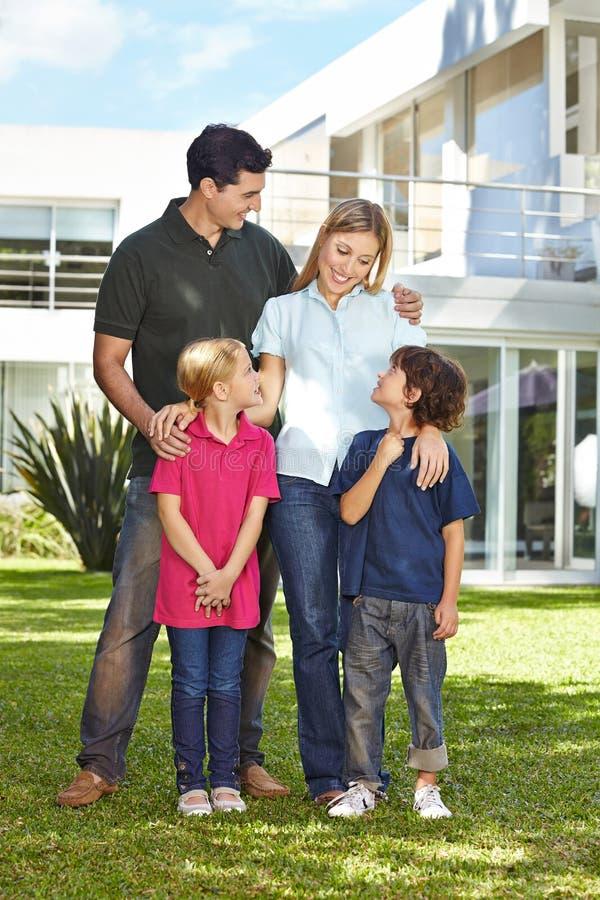 Familie met twee kinderen voor huis royalty-vrije stock afbeelding