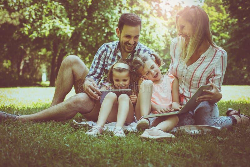 familie met twee kinderen in weide die laptop en digita gebruiken stock foto