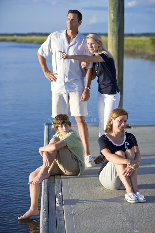 Familie met twee tienerkinderen op dok door water stock foto's