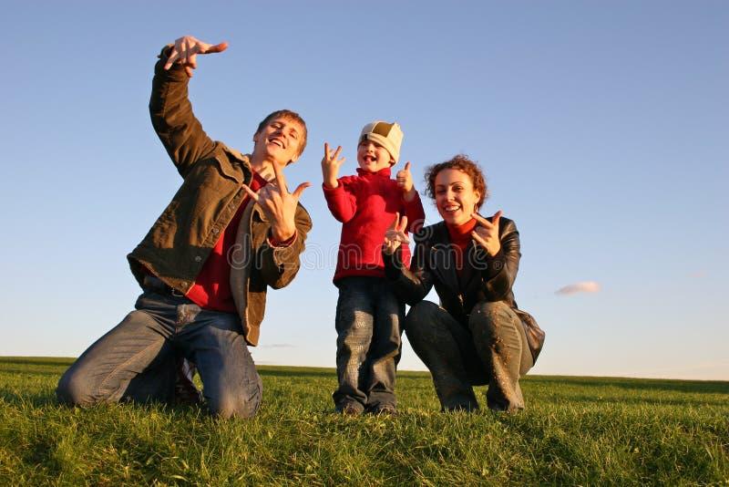 Familie met vingers op gras stock foto