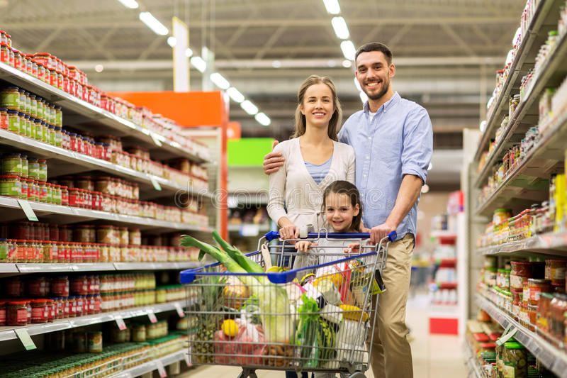 Familie met voedsel in boodschappenwagentje bij kruidenierswinkelopslag royalty-vrije stock afbeeldingen