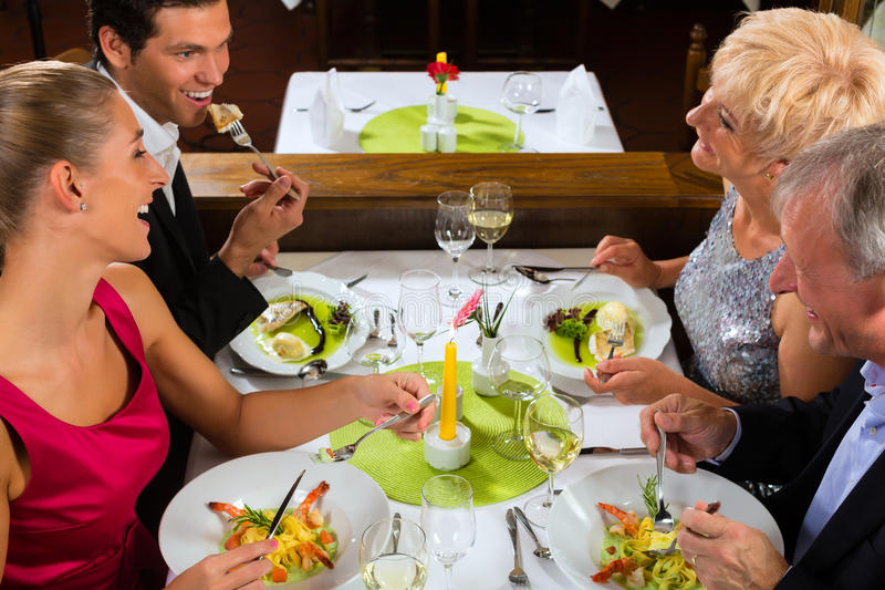 Familie met volwassen jonge geitjes in Restaurant stock afbeelding
