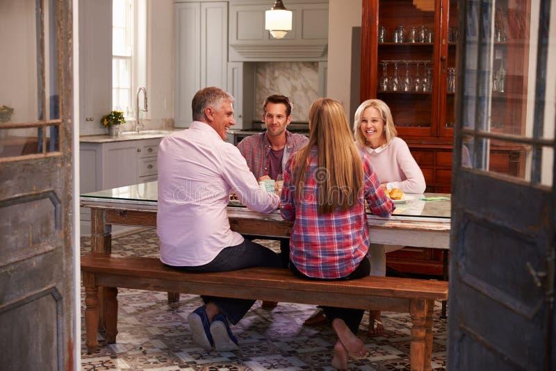 Familie met Volwassen Nakomelingen die van Maaltijd thuis samen genieten stock afbeelding