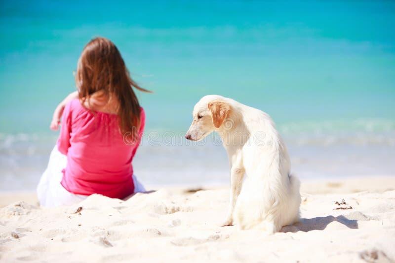 Familie met witte hond op tropisch strand royalty-vrije stock foto's