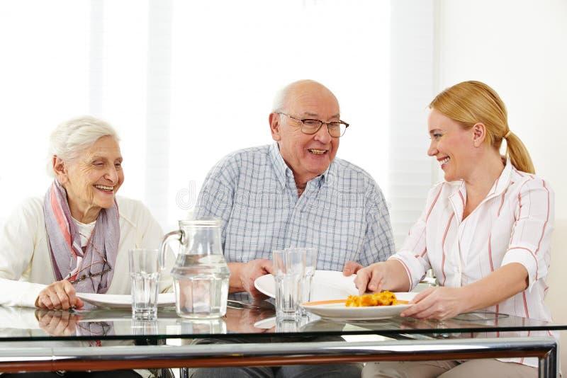 Familie mit dem älteren Paaressen lizenzfreies stockbild