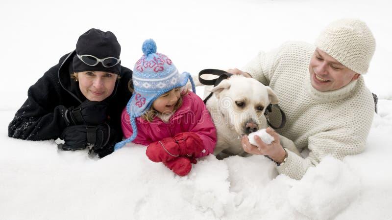 Familie mit dem Hund, der im Schnee spielt lizenzfreie stockbilder
