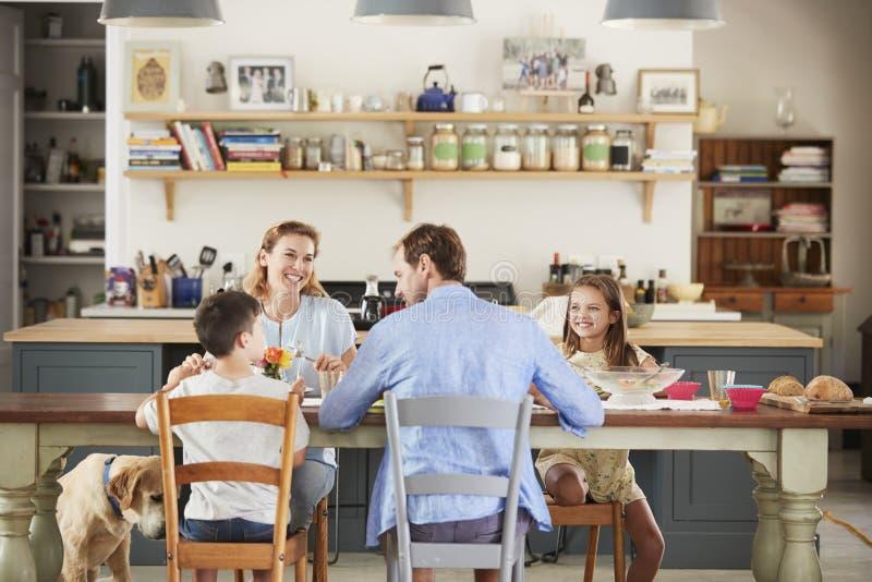 Familie mit dem Hund, der zusammen am Tisch in der Küche isst stockbild