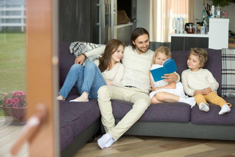 Familie mit dem Kinderlesebuch, das zu Hause auf Sofa sitzt stockbild