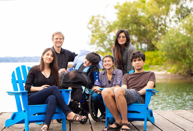 Familie mit dem speziellen Bedarfskind, das draußen zusammen in der Summe sitzt lizenzfreies stockbild
