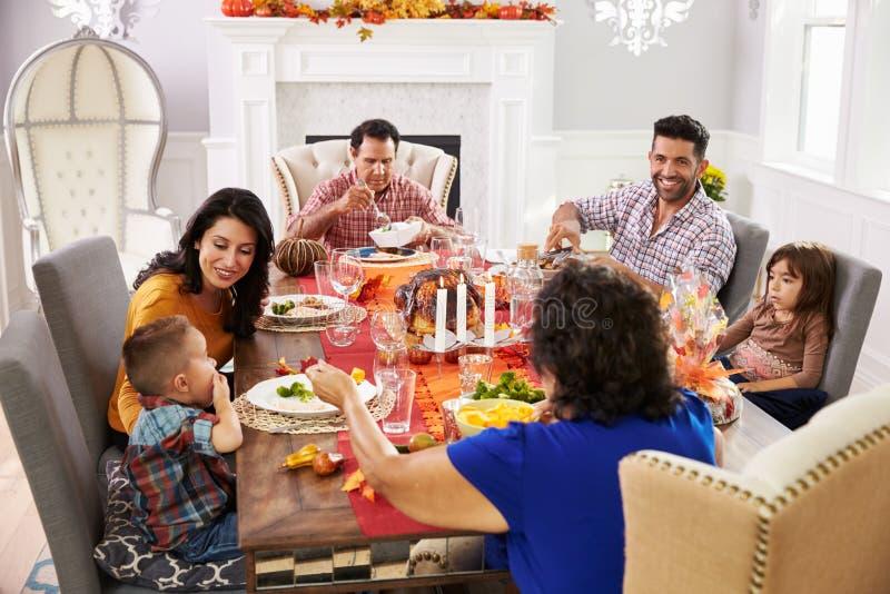 Familie mit den Großeltern, die bei Tisch Danksagungs-Mahlzeit genießen lizenzfreie stockfotos