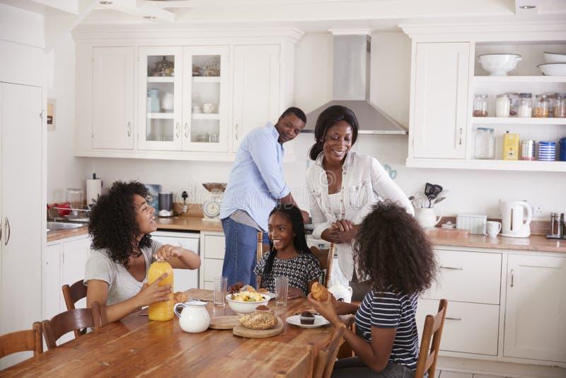 Familie mit den Jugendkindern, die Frühstück in der Küche essen lizenzfreies stockbild