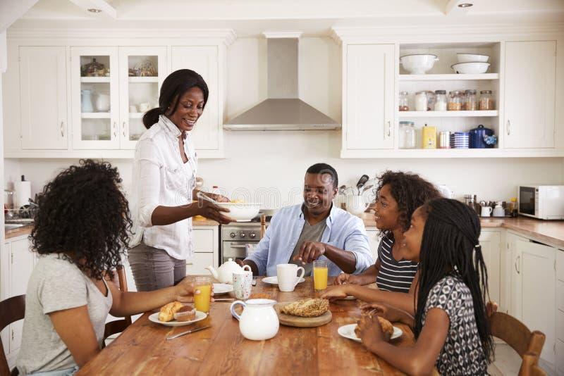 Familie mit den Jugendkindern, die Frühstück in der Küche essen lizenzfreies stockfoto