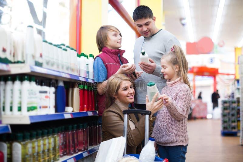 Familie mit den Kindern, die Shampoo im Supermarkt kaufen stockbilder
