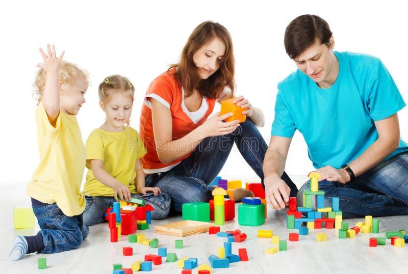 Familie mit den Kindern, die Spielwaren-Blöcke, Kindereltern auf Weiß spielen stockfoto