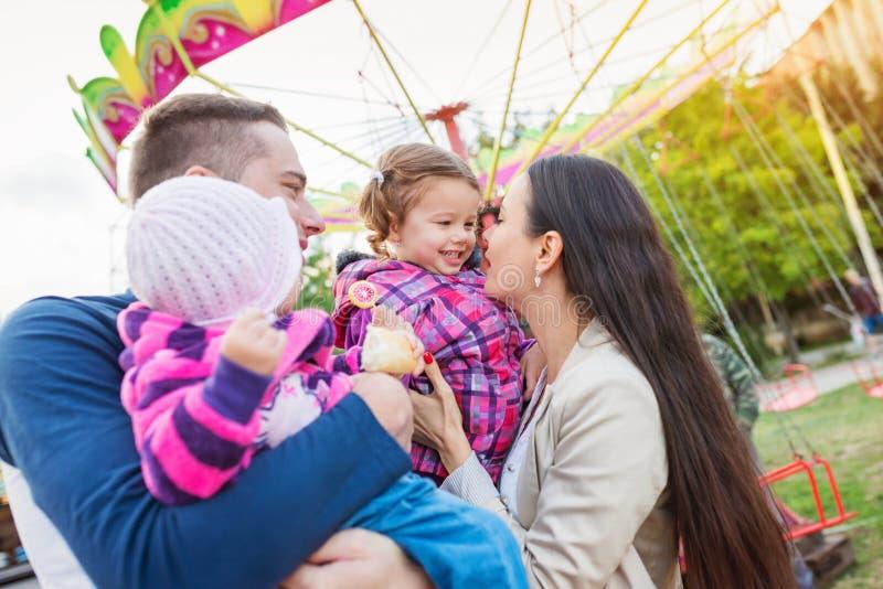 Familie mit den kleinen Mädchen, die Zeit an der Spaßmesse genießen lizenzfreies stockbild