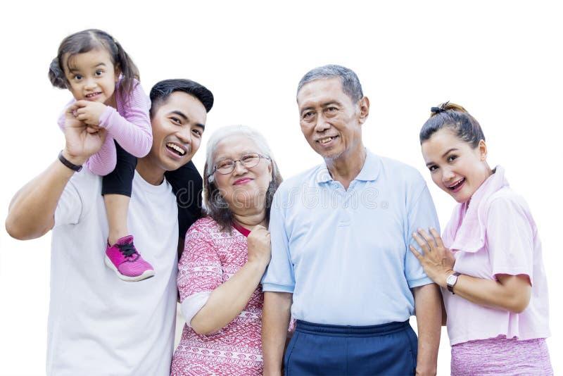 Familie mit drei Generationen, die auf Studio lächelt stockbilder
