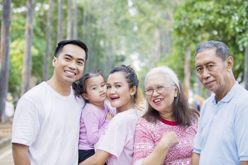 Familie mit drei Generationen, die an der Kamera lächelt stockfoto