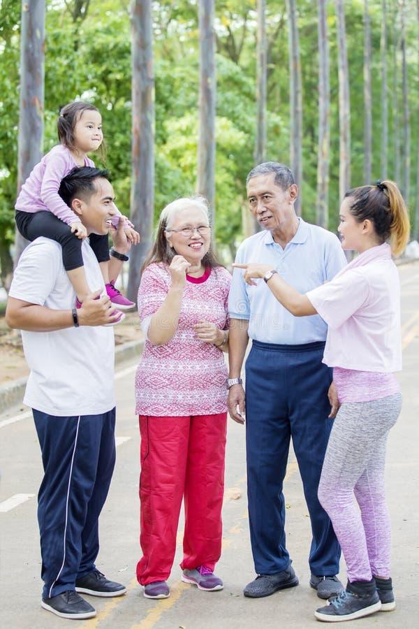 Familie mit drei Generationen, die im Park spricht lizenzfreie stockbilder
