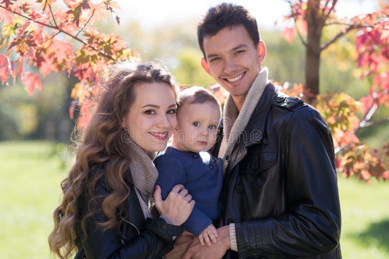 Familie mit einem Baby im Herbstpark stockfotos