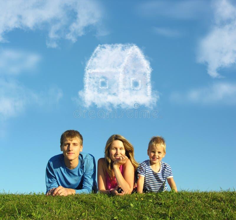 Familie mit Jungen auf Gras und Traum bewölken Haus stockfotografie