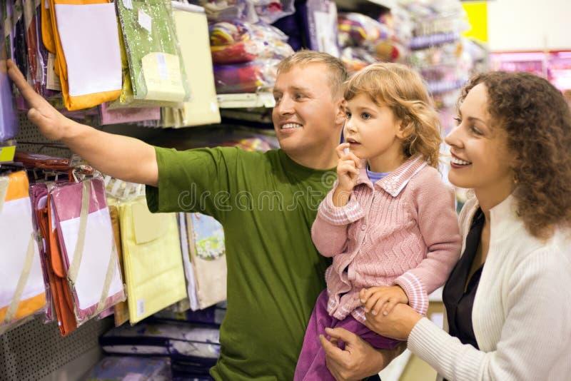 Familie mit Kaufbettwäsche des kleinen Mädchens im Supermarkt stockbilder