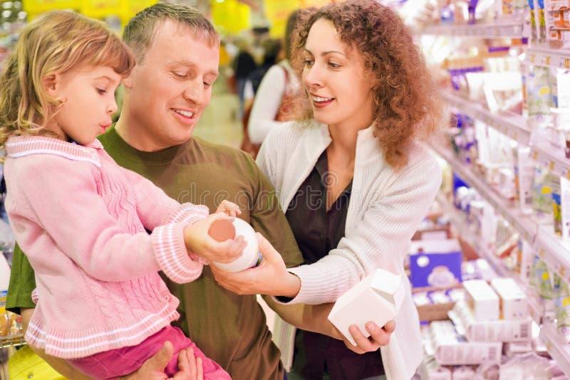 Familie mit Kaufmilch des kleinen Mädchens im Supermarkt lizenzfreie stockfotos