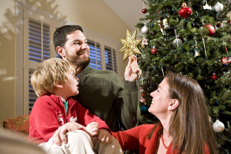 Familie mit Kind durch Weihnachtsbaum stockfoto