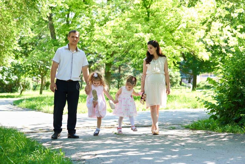 Familie mit Kind und schwangere Frau gehen in Sommerstadtpark stockfotos